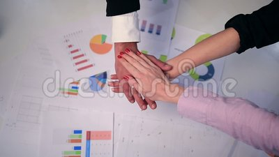 Business partners making pile of hands at meeting stock footage