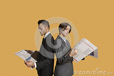 Business partners standing back to back while reading newspaper