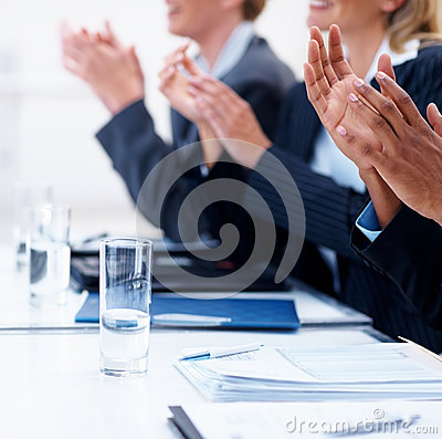 Business people applauding at a seminar by glass
