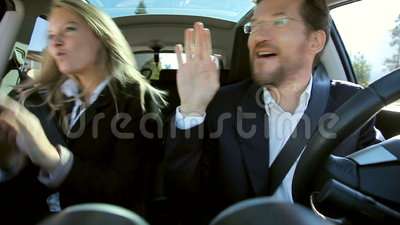 Business people dancing in car happy. Business people in car having fun driving after success