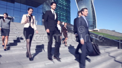 Business people go down stairs. Team of diverse business people go down the stairs of company office building