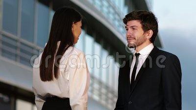Business People Handshake - business people shaking hands. Handshake between man and woman outdoors by business building. Professional shot in 4K resolution stock video footage