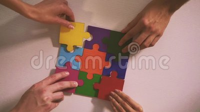 Business people join puzzle pieces in office. Concept of teamwork and partnership. Business people join puzzle pieces in a modern office. Concept of teamwork and stock footage