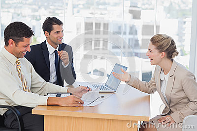 Business people laughing with interviewee