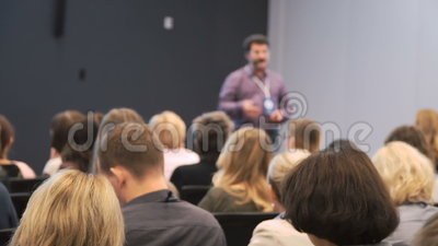 Business People Seminar Conference Meeting Office Training Concept. Spectators sit in the lobby of the conference hall. Speaker shows slides on the projector stock footage