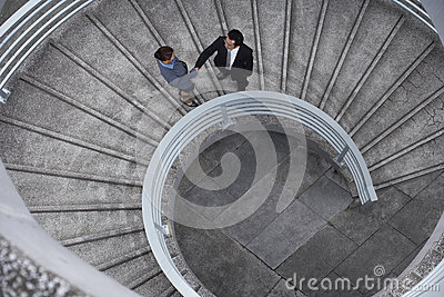 Business People Shaking Hands On Spiral Staircase