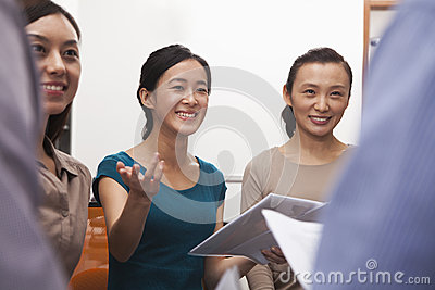 Business people smiling and having meeting in the office, gesturing