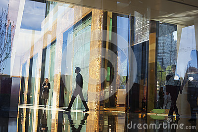 Business People walking through the lobby of an office building on the other side of a glass wall