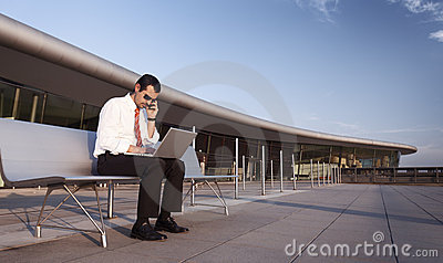 Business person busy on phone and laptop.