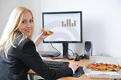 Business person eating pizza at computer