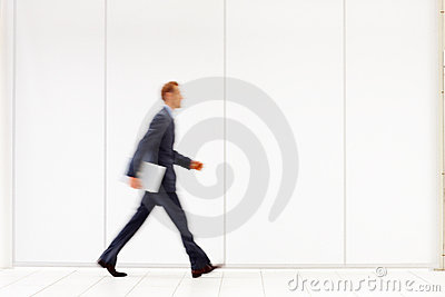 Business person holding a laptop and walking