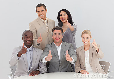Business team celebrating a success with thumbs up