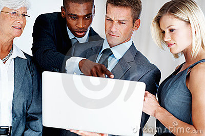 Business team discussing while looking at laptop