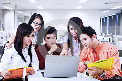 Business team discussion on laptop at office