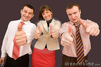 Business team in formal suits with thumbs up