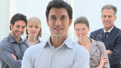 Business team. Happy smiling group of business people standing together at office with leadership in the foreground. Portrait of successful businessman with