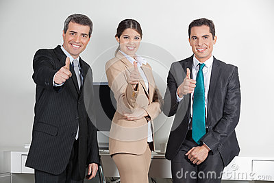 Business team holding thumbs up