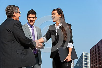 Business team shaking hands over deal outdoors.