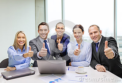 Business team showing thumbs up in office