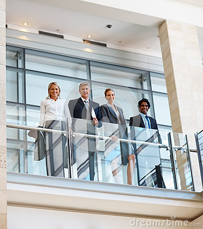 Business team standing by a glass railing
