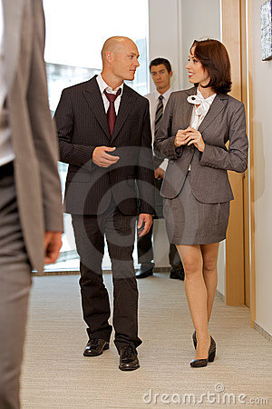 Business team walking thru corridor and talking