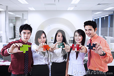 Business teamwork and puzzle pieces at office