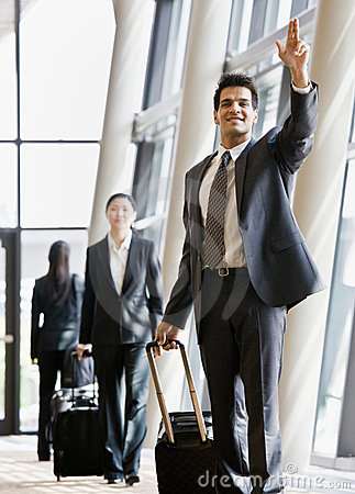 Business traveler pulling suitcase and gesturing