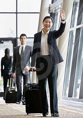 Business traveler pulling suitcase and waving