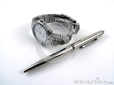 Business watch near a silver ball pen