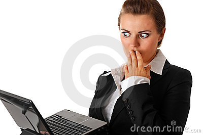 Business woman amazedly looks in laptops screen