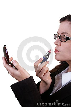 Business woman applying red lipstick