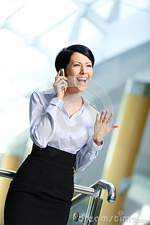 Business woman in business suit talks on phone
