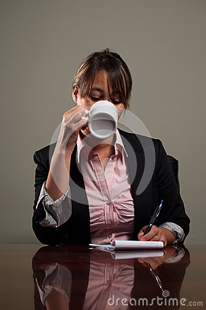 Business woman drinking coffee during meeting
