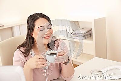 Business woman enjoying coffee at modern office
