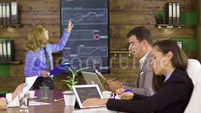 Business woman in a finance meeting pointing at graphs on tv screen. Business woman holding a presentation for her young team stock footage