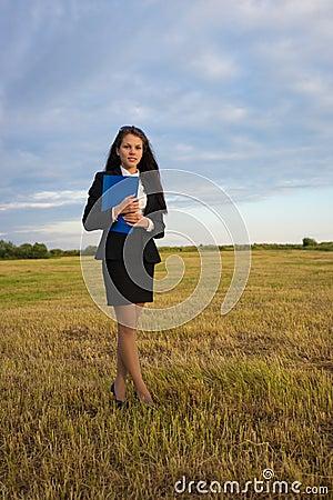 Business woman on green field