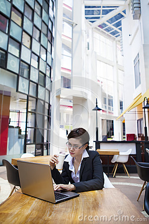Business woman having coffee break with laptop