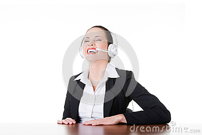 Business woman with headphones laughing.