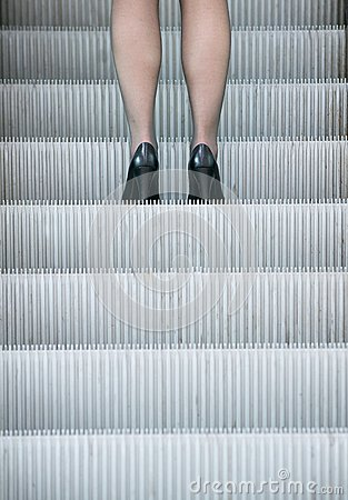 Business woman in high heels standing on escalator
