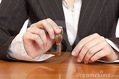 Business woman holds house key for handing over