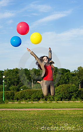 Business woman jumping with balloons