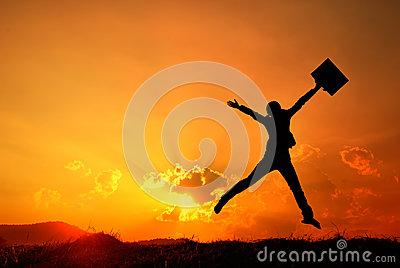 Business woman jumping and sunset silhouette