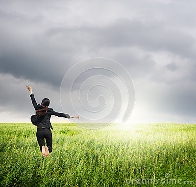 Business woman jumping to raincloud in grassland