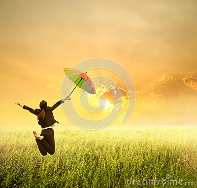 Business woman jumping to sunset with red umbrella