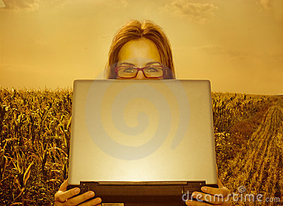 Business woman with laptop in a field