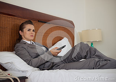 Business woman laying on bed and watching tv