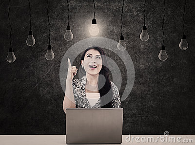 Business woman with light bulbs and laptop