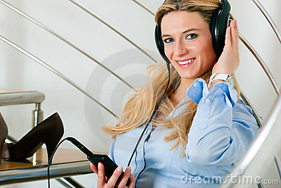 Business woman listening music at home