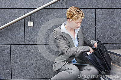 Business woman looking for files in briefcase