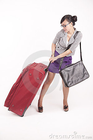 Business woman pulling heavy suitcase